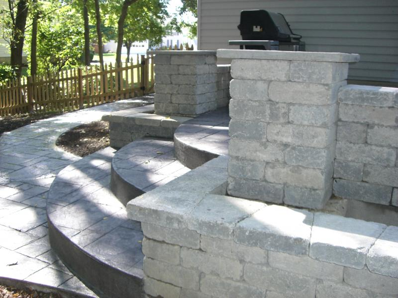 Column, planter and retaining wall with stamped concrete steps and raised patio