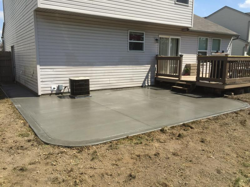 Broom finish patio with proper yard grading ready for grass and/or mulch beds.