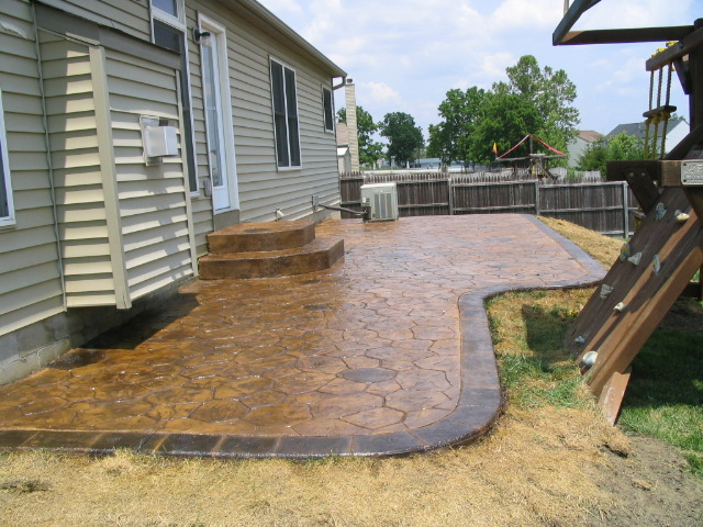 Random Stone stamped concrete patio with acid stained boarder