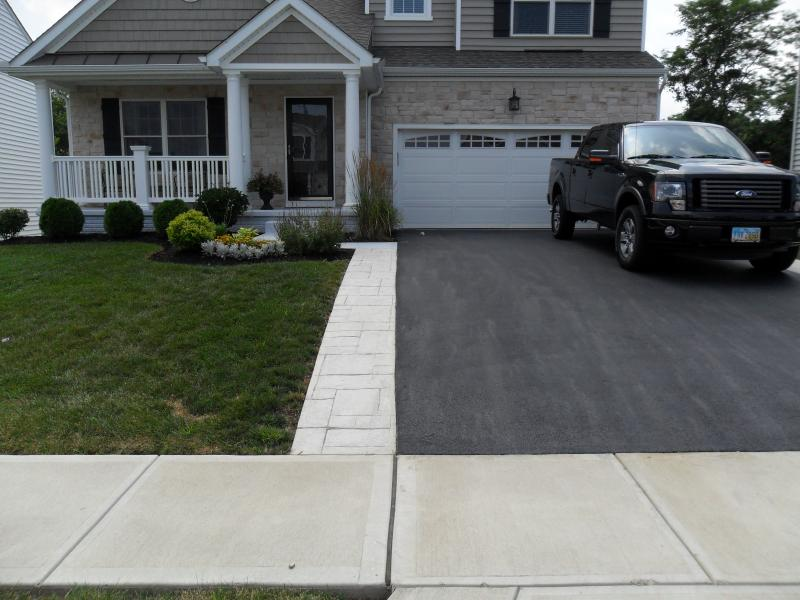 Stamped concrete without color. Great addition to an asphalt driveway.